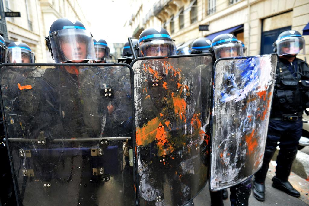 "Riot police officers hold shields covered in paint during a protest called by seven labour unions and students against labour and employment law reform on May 26, 2016 in Bordeaux, southwest France. Fresh rallies were due to be held May 26 in Paris and other cities in the latest bout of social unrest that started three months ago and has frequently turned violent. Under intense pressure, Prime Minister Manuel Valls vowed the labour law would not be withdrawn, but said it might still be possible to make ""changes"" or ""improvements"". / AFP PHOTO / GEORGES GOBET"