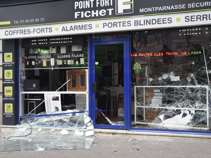 A photo taken on June 14, 2016 shows the broken window of a shop during a demonstration against proposed labour reforms in Paris. Several hundred masked protesters hurled objects at police on June 14 during a demonstration in Paris against a contested reform of French labour laws, authorities said. / AFP PHOTO / DOMINIQUE FAGET