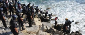 A group of 300 migrants and asylum seekers at the border town of Ventimiglia forces a police cordon, jumps into the sea and swam to France on Friday 05 August 2016. Some of the asylum seekers simply ran across the border, breaking through a French police cordon and onto the crowded beaches beyond. Italian and French police fired tear gas but were unable to stop them. ANSA / FABRIZIO TENERELLI